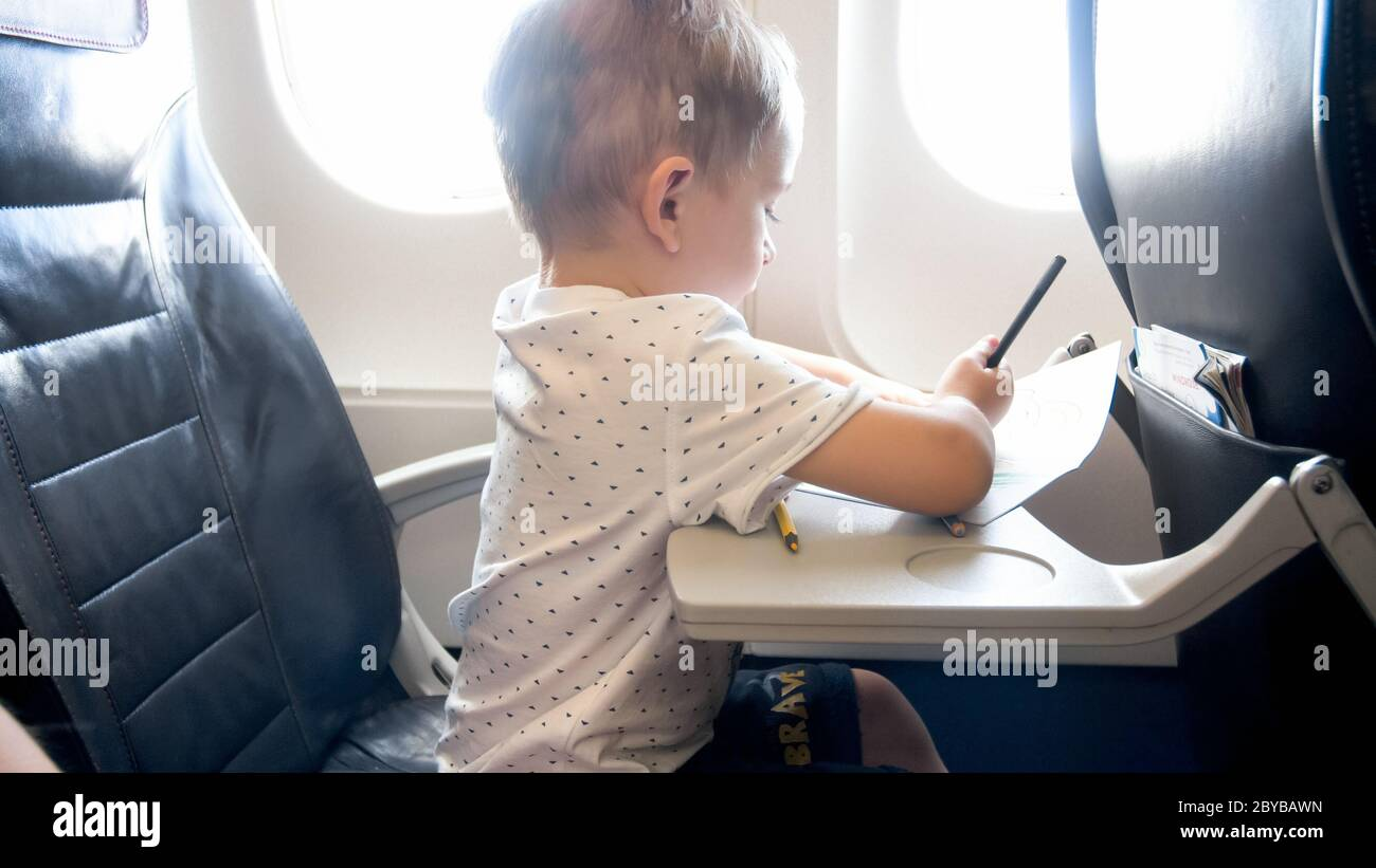 Cute Little Boy Drawing Picture With Pencils While Flying In Airplane Stock Photo Alamy