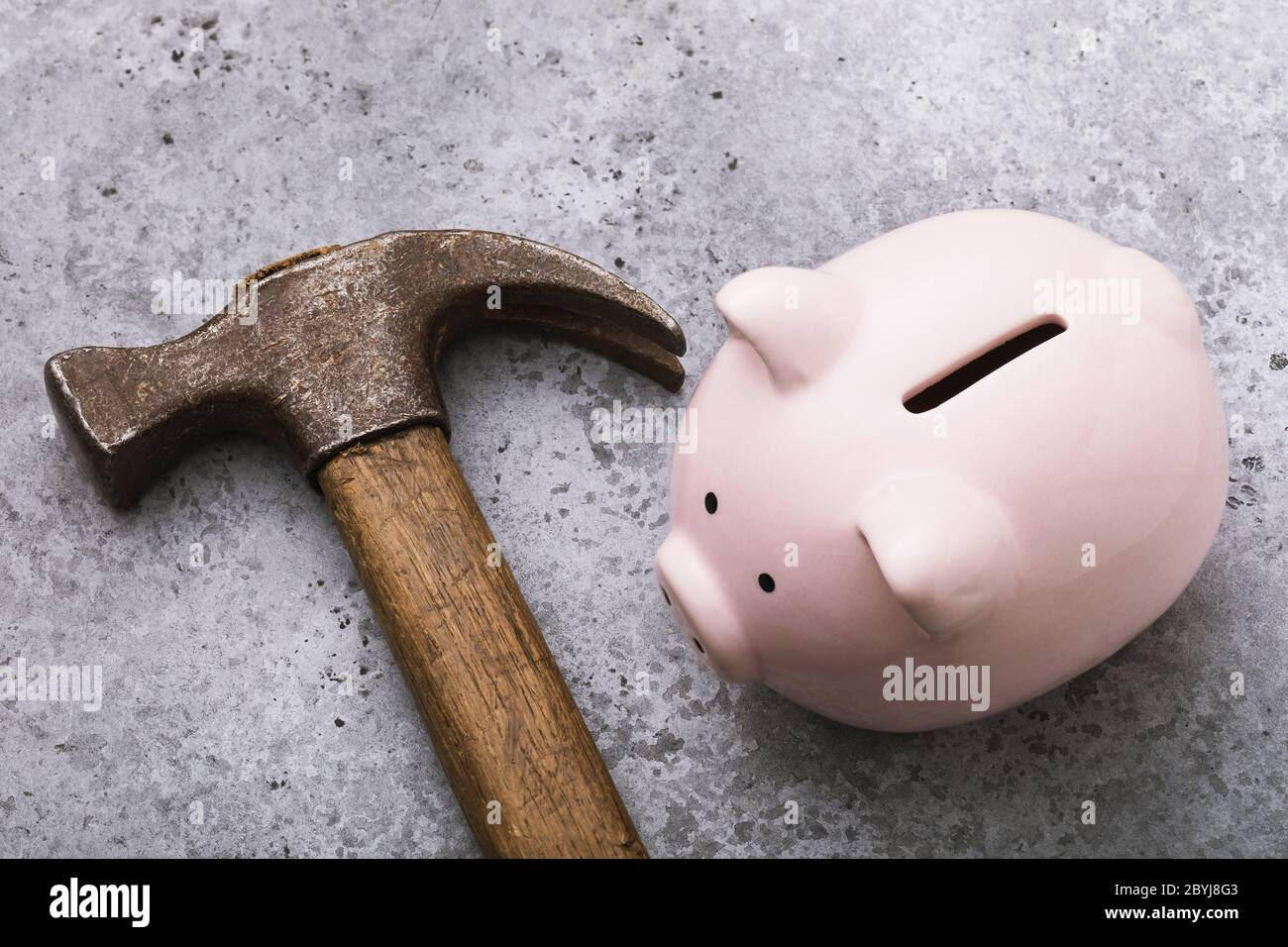 Pink piggy bank and hammer on the table, closeup. Crisis concept Stock Photo