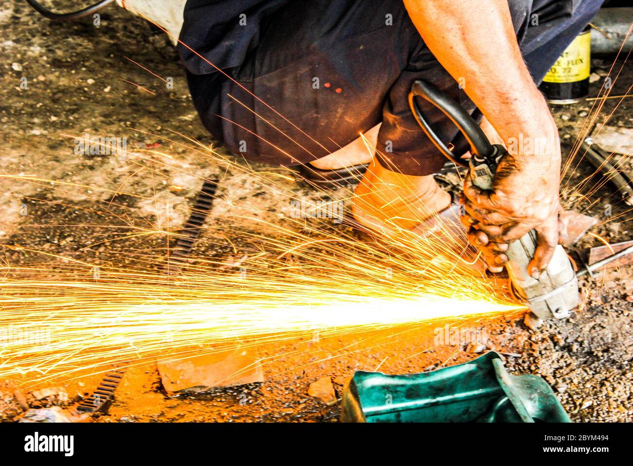mechanics repairing steel sparks fire light in auto car shop station Stock Photo