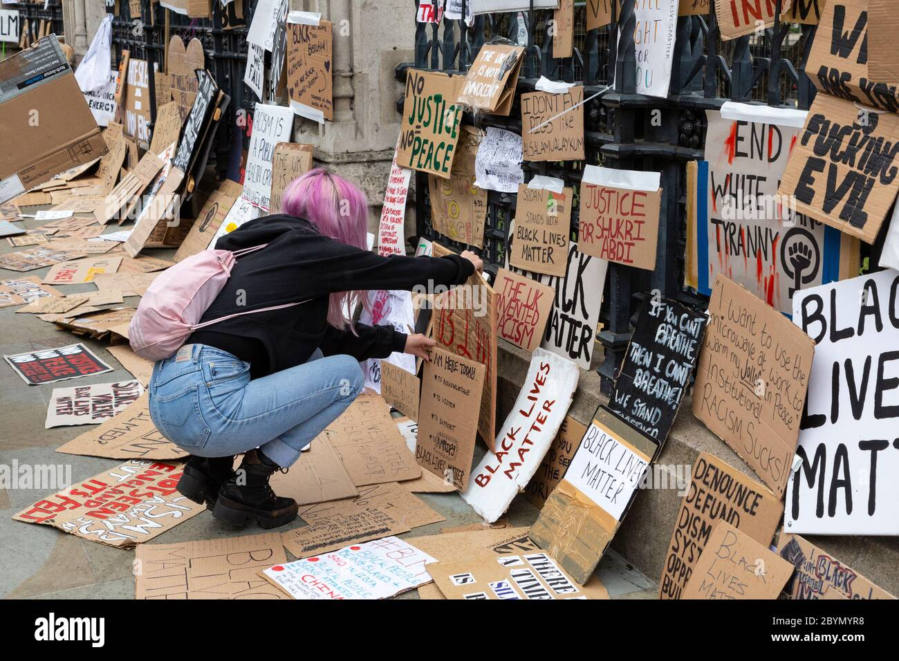 A protester lays a sign outside the Palace of Westminster after a Black Lives Matters protest, Parliament Square, London, 7 June 2020 Stock Photo