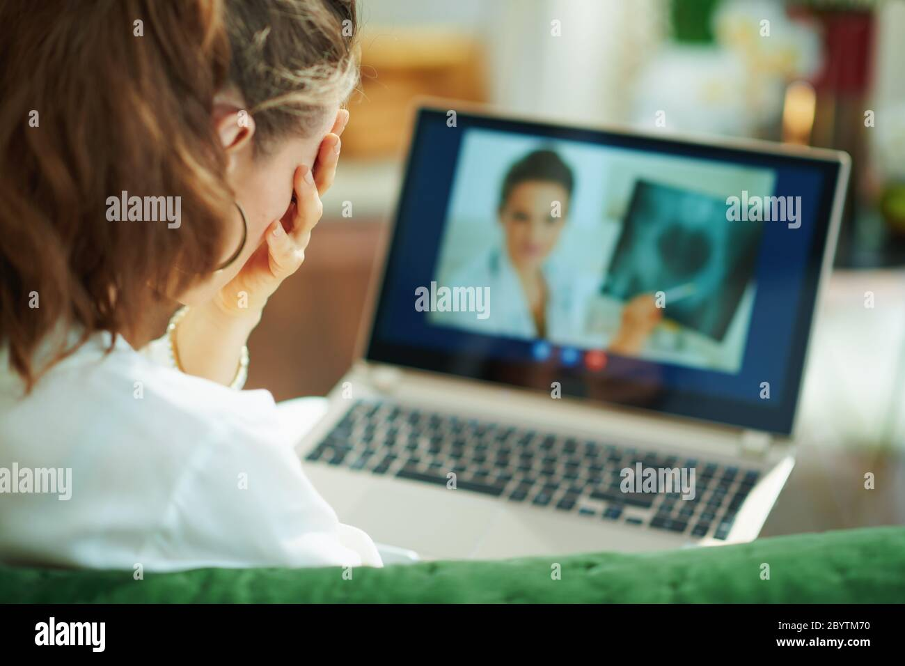 Seen from behind woman speaking with doctor using tele health technology on a laptop while sitting on a couch in the house in sunny day. Stock Photo
