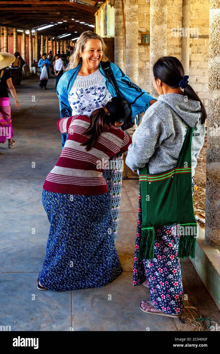 A Tourist Tries On A Traditional Burmese Longyi Sarong Helped By Two Local Women Thaung Thut Market Lake Inle Shan State Myanmar Stock Photo Alamy