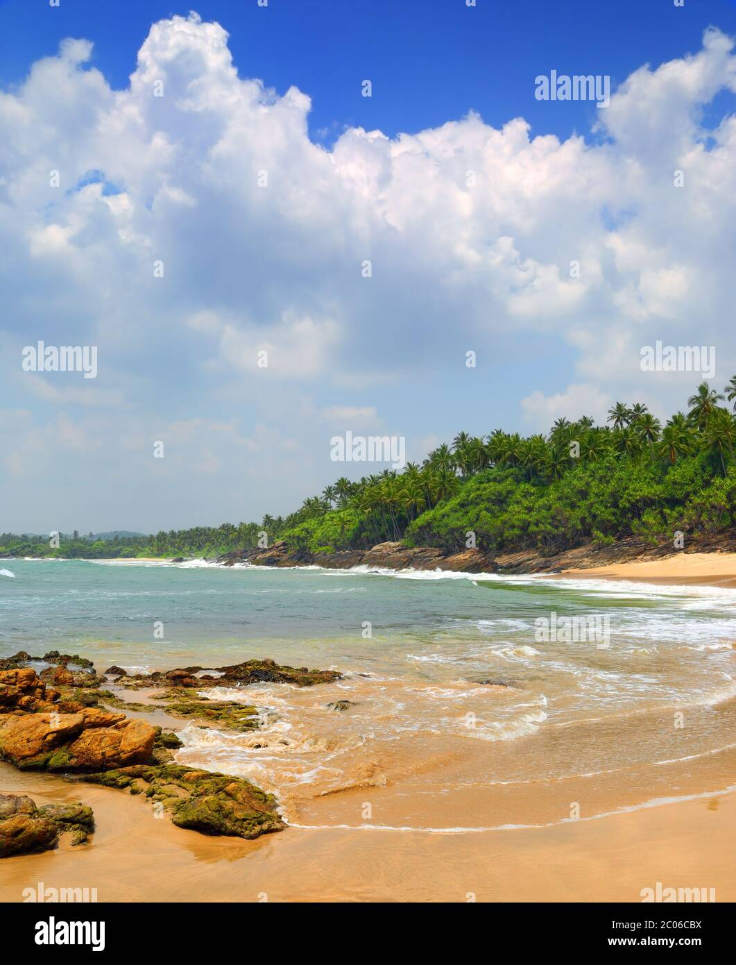 sea waves on tropical beach with stones and rocks Stock Photo