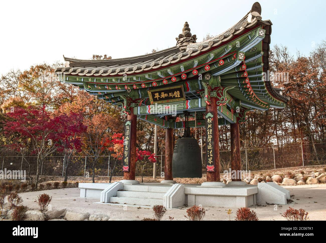 Large Buddhist Bell in a Pavilion with Green and Red Ornaments in the DMZ in South Korea Stock Photo