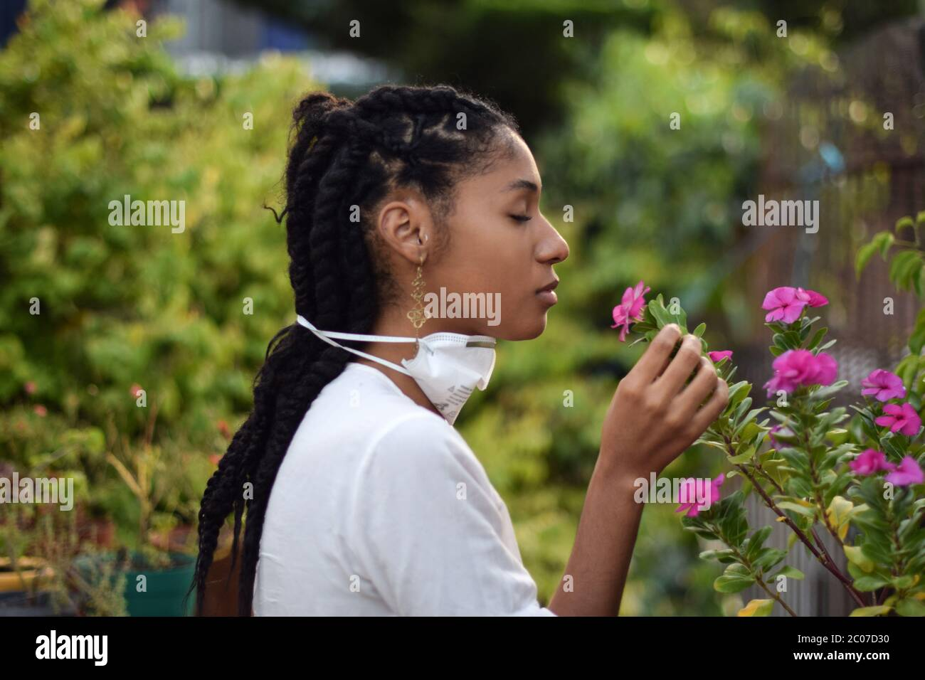 Young woman takes face mask off to smell the flowers Stock Photo