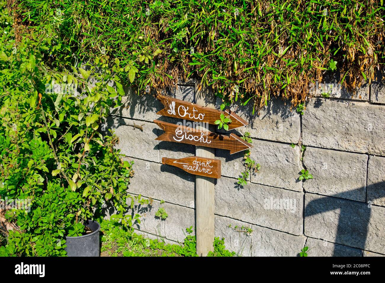 A handmade wooden sign with a lizard nearby in an Italian bed and breakfast points to games, garden or drink machine in Monterosso al Mare, Italy Stock Photo