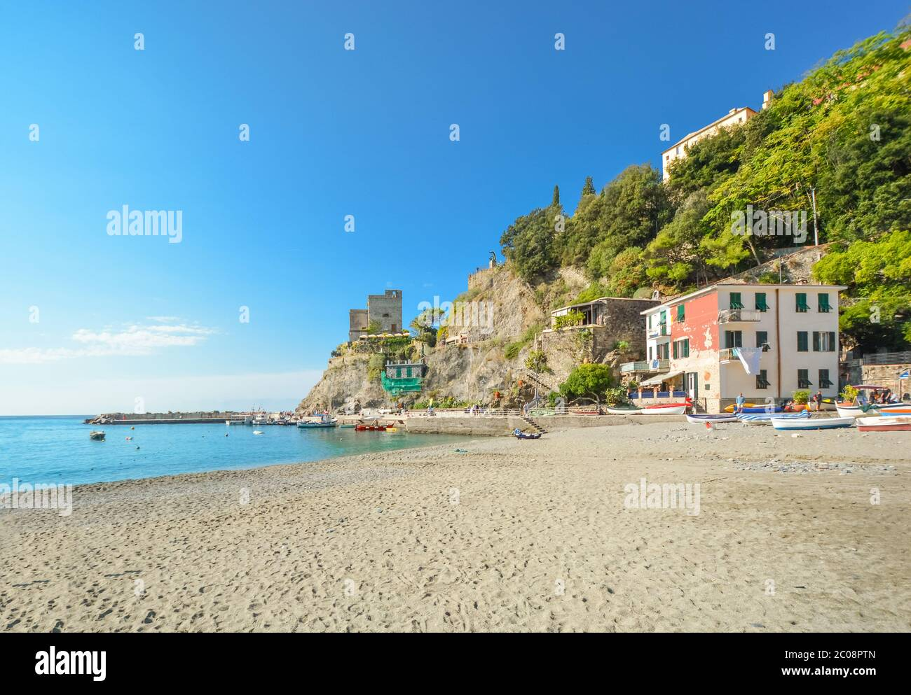 The ruins of the Aurora Tower Castle at Monterosso al Mare rise above the sandy beach and coast in Cinque Terre Italy on the Ligurian Coast Stock Photo