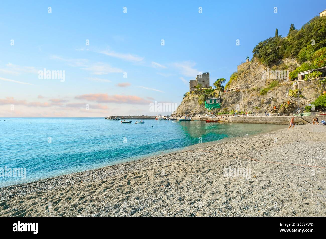 The ruins of the Aurora Tower and Castle at Monterosso al Mare rise above the sandy beach and coast in Cinque Terre Italy on the Ligurian Coast Stock Photo