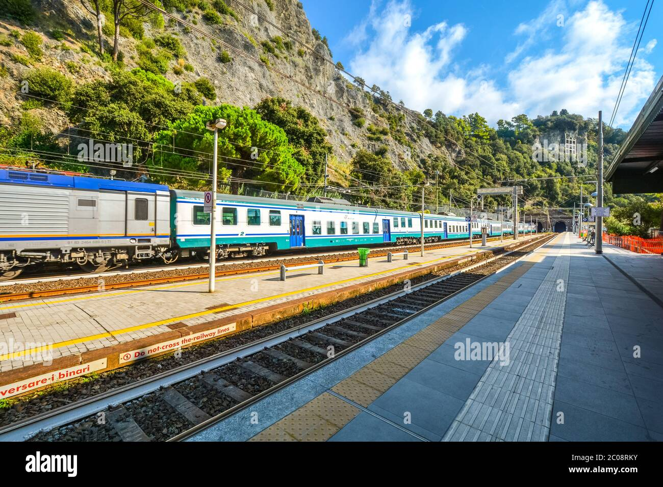 A moving Trenitalia train passes by the tracks at the railway station in the afternoon at Monterosso Al Mare, Cinque Terre Italy Stock Photo