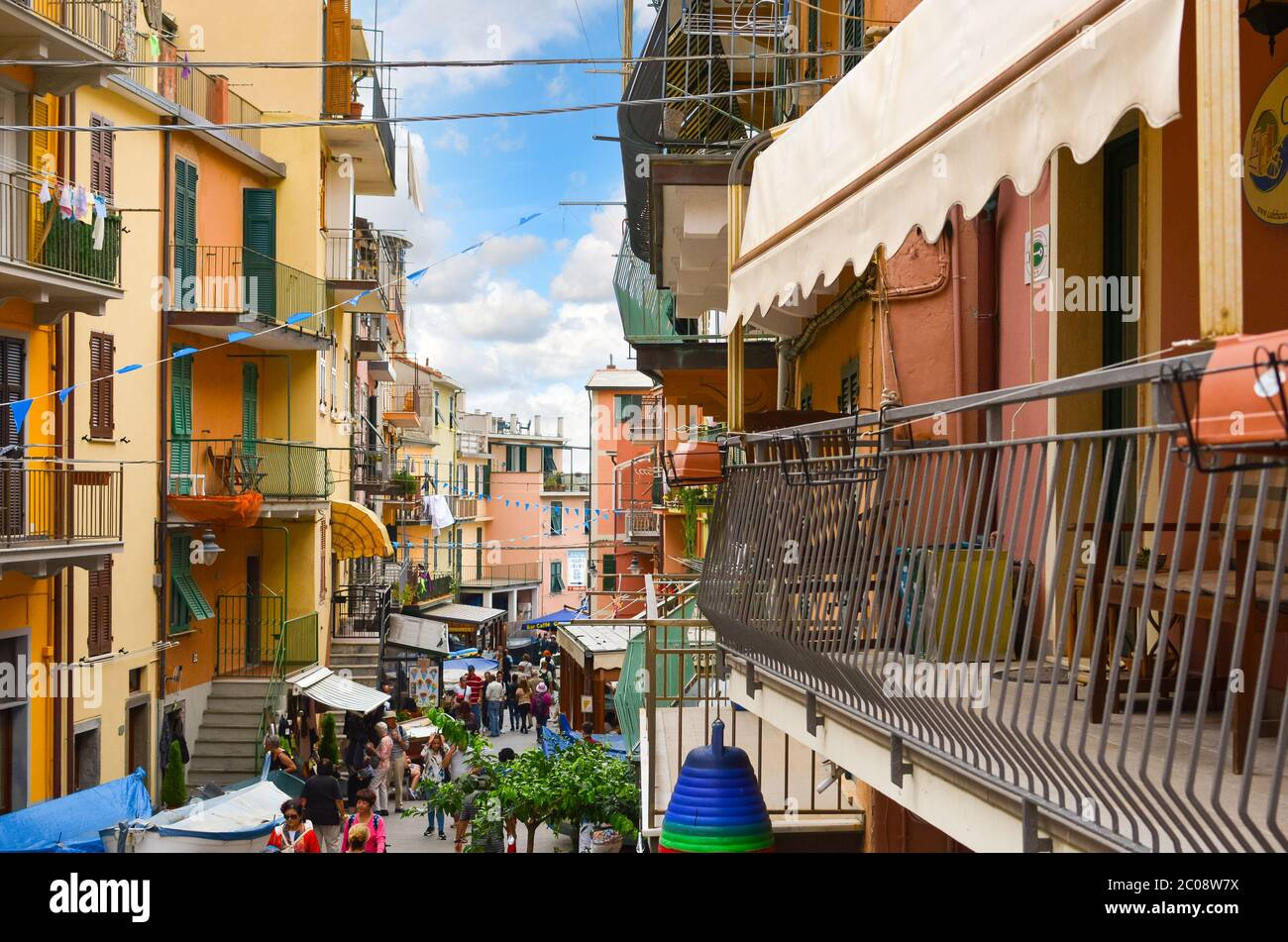 Balconies overlook the main street of Manarola Italy, part of the Cinque Terre, as tourists and locals enjoy an afternoon. Stock Photo