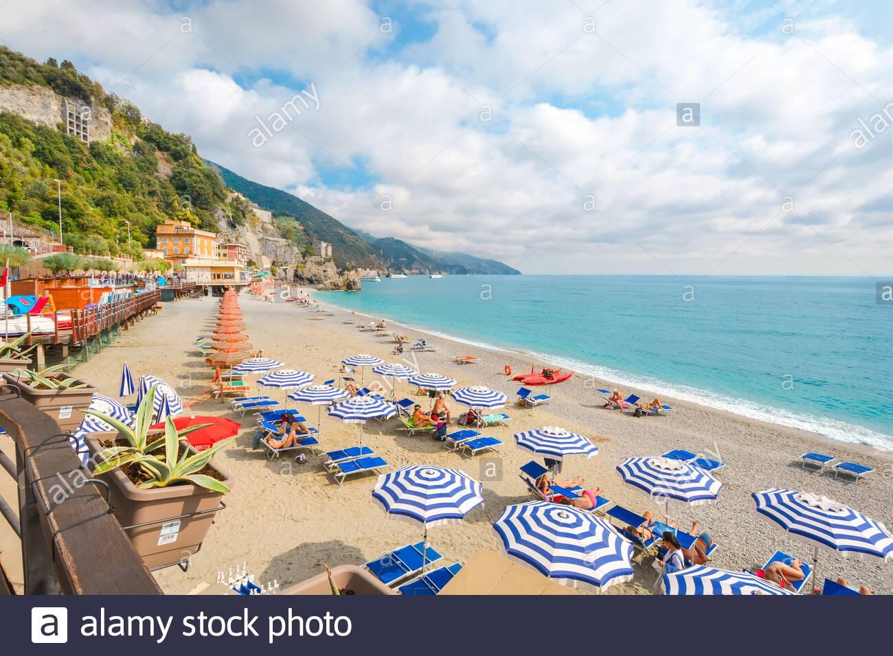 The sea and sandy beach Spiaggia di Fegina at the Cinque Terre Italy resort village of Monterosso al Mare with tourists enjoying the Italian Riviera Stock Photo