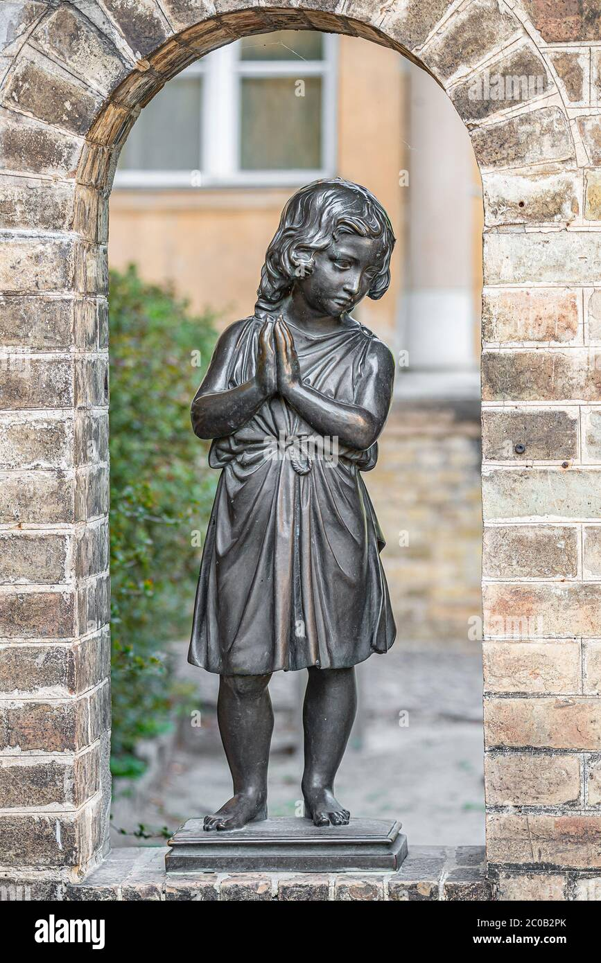 Old statue of a beautiful small girl praying in downtown park of Potsdam, Germany, portrait, details Stock Photo