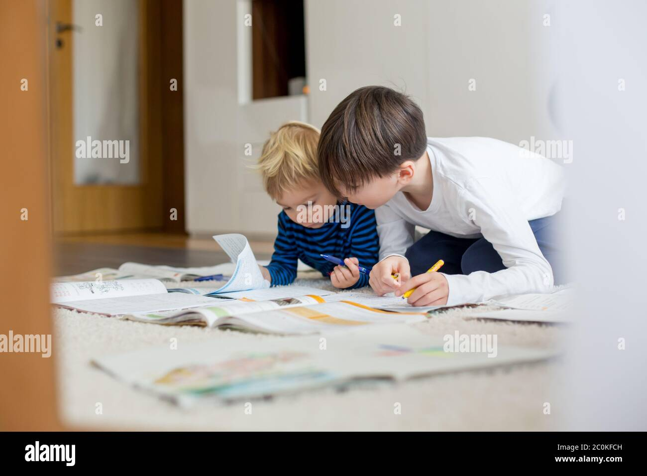 Child, doing school work on the floor at home while in quarantene, kid homeschooling Stock Photo