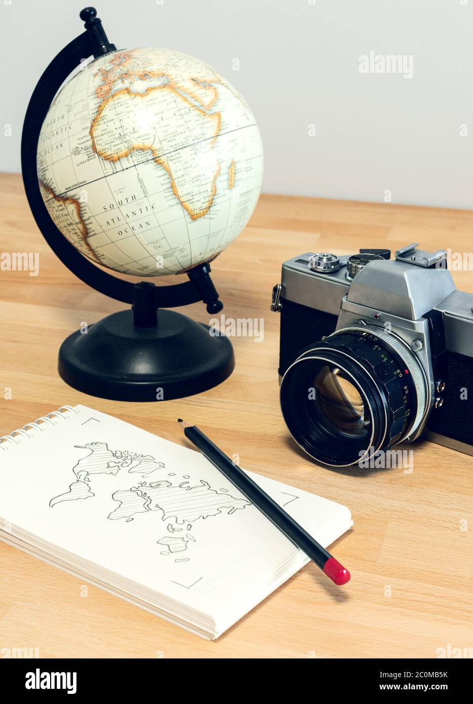 Camera, world globe and notebook with world map on a wooden desk. Travel concept image: planning a journey. Stock Photo