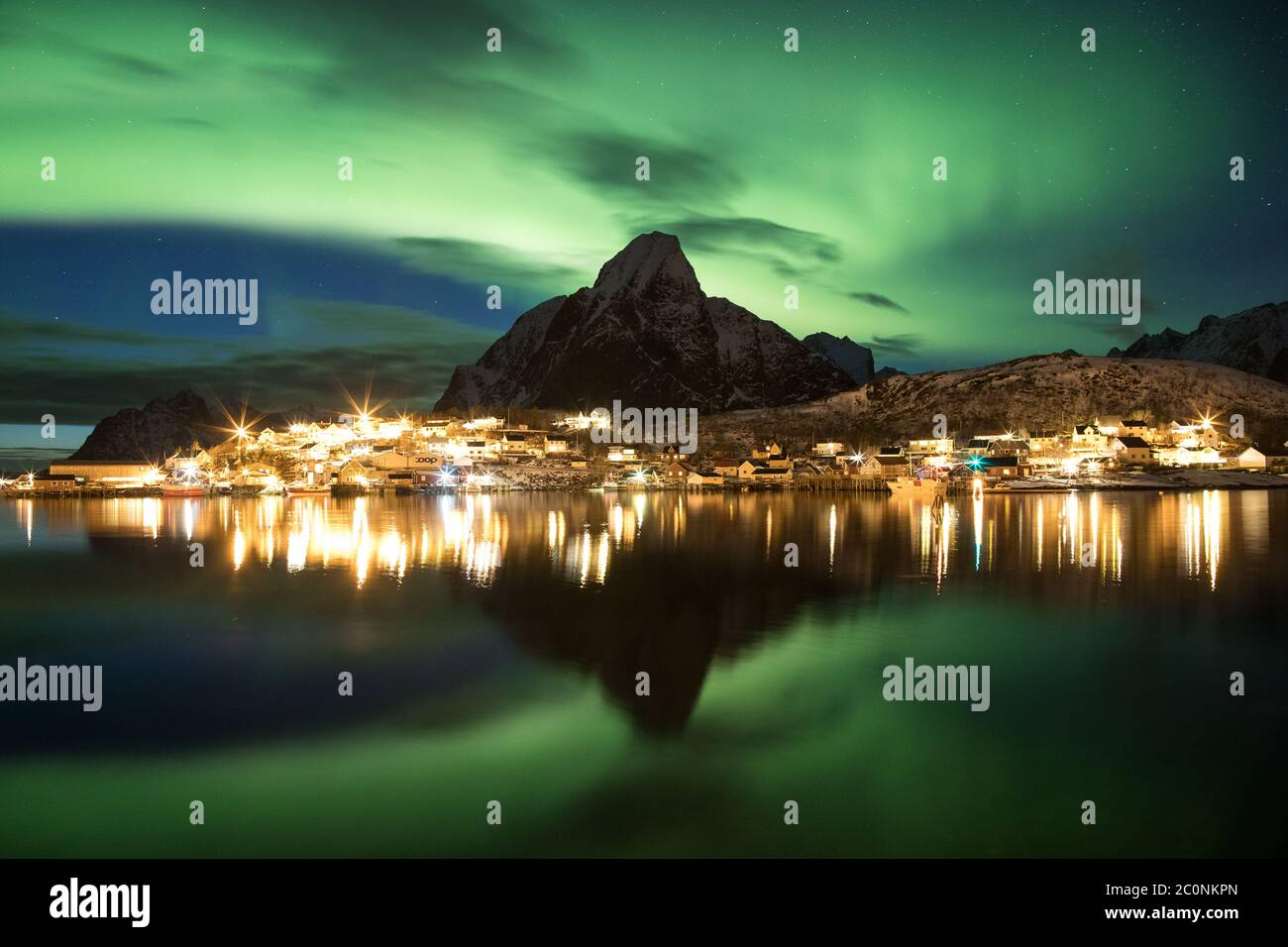 A stunning display of the northern lights over Olstinden mountain in Reine. Stock Photo