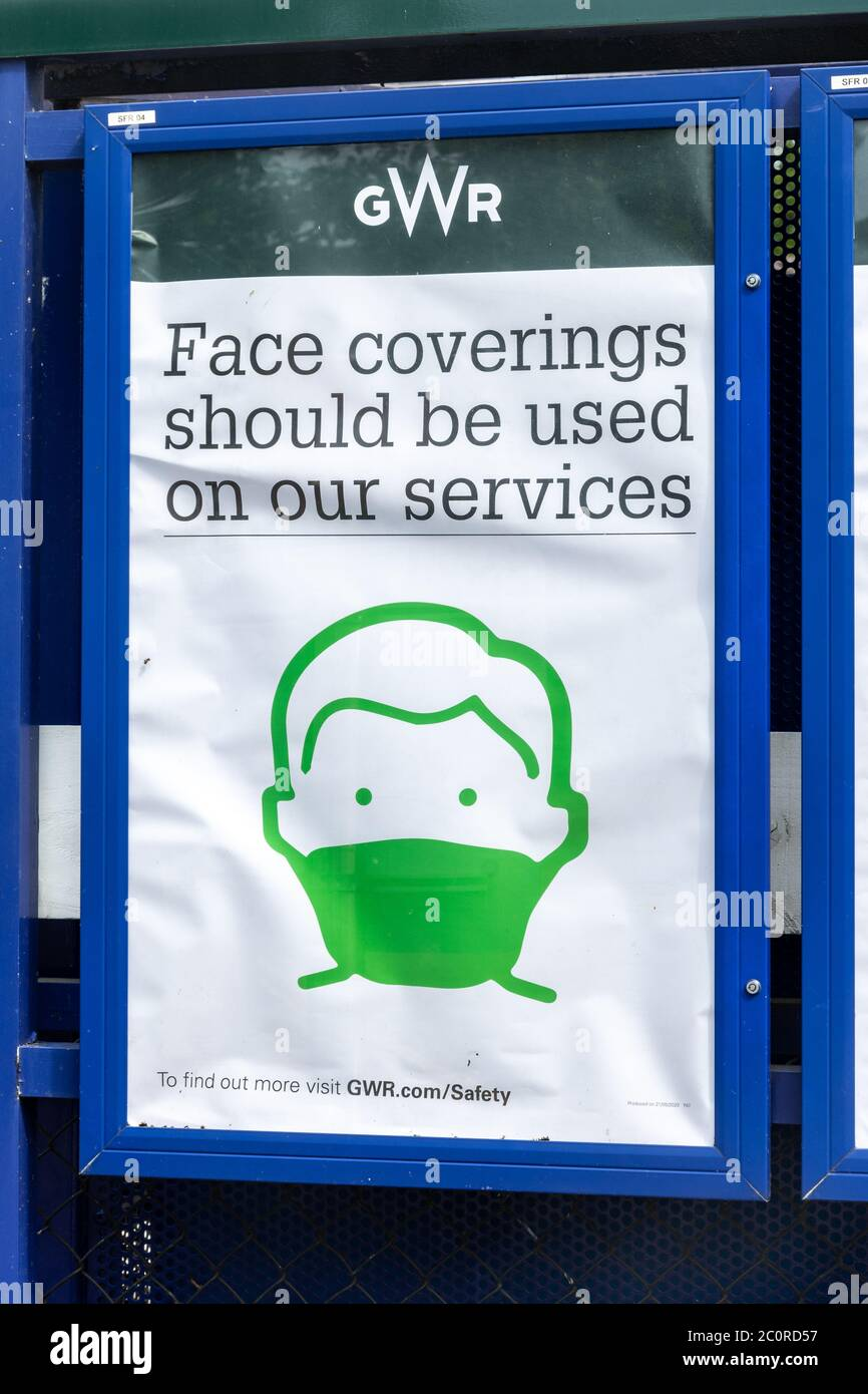 Notice at UK railway station informing passengers Face coverings should be used on trains during the coronavirus covid-19 pandemic, June 2020 Stock Photo