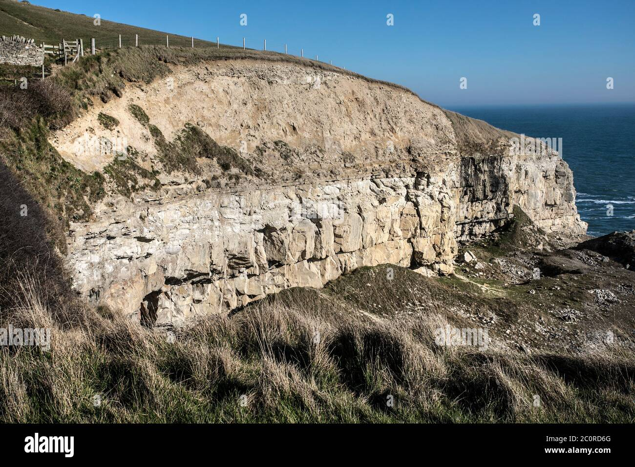 Crumbling cliffs in Dorset with rock strata on Jurassic Coast, with rough seas Stock Photo