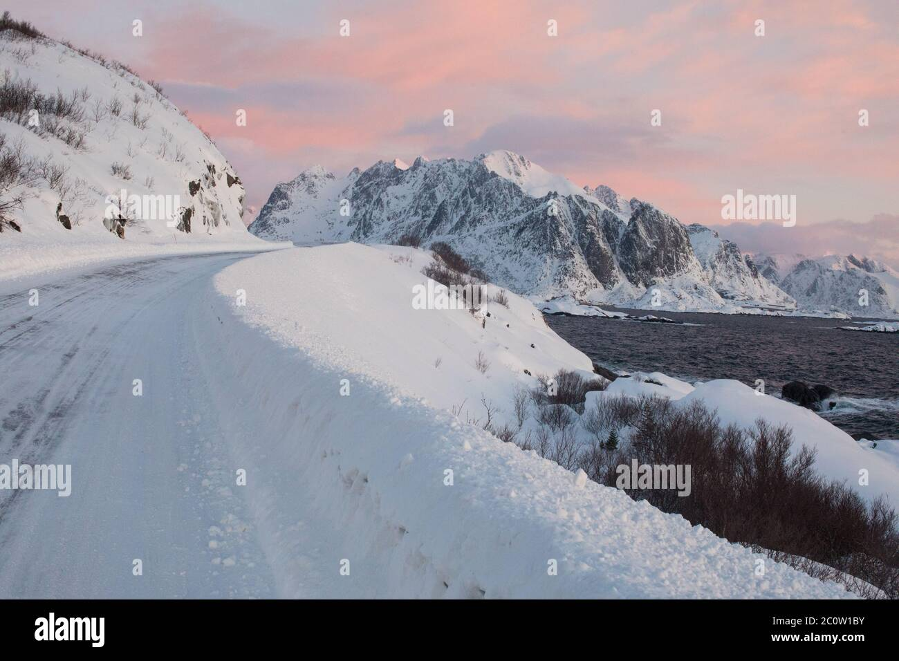 Pink skies and ice mountain roads in Norway. Stock Photo