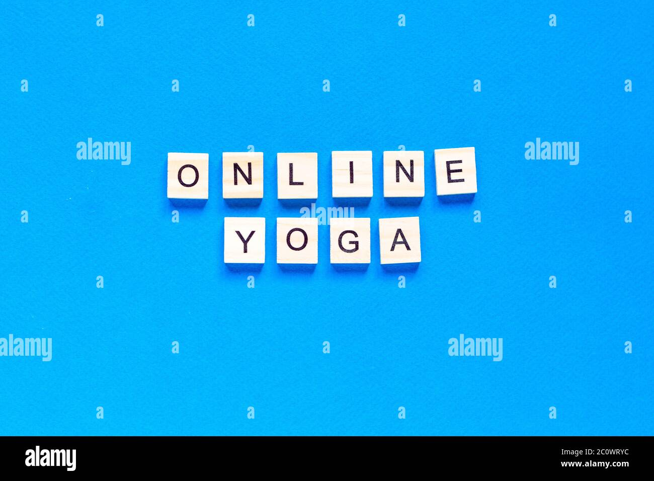 The word ONLINE YOGA written in wooden letterpress type on a blue background. top view. flat layout. Stock Photo