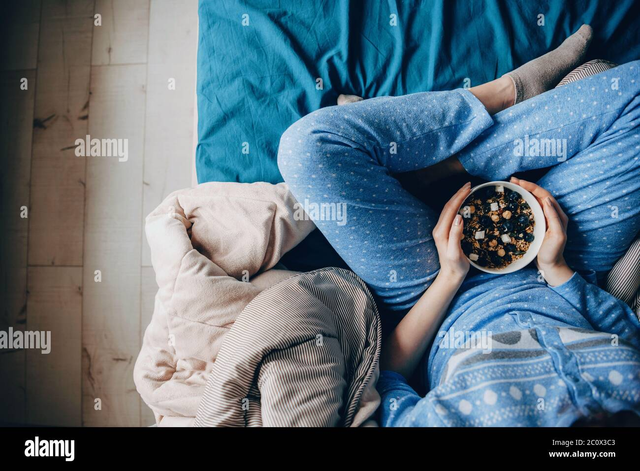 Upper view photo of a woman wearing pajama with healthy habits eating cereals Stock Photo