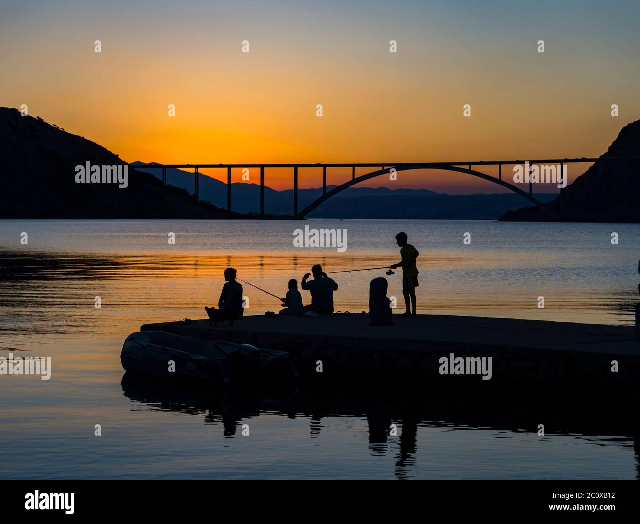 Family together dusk evening free time fishing bridge mainland to island Krk in background silhouettes silhouetting silhouette Stock Photo