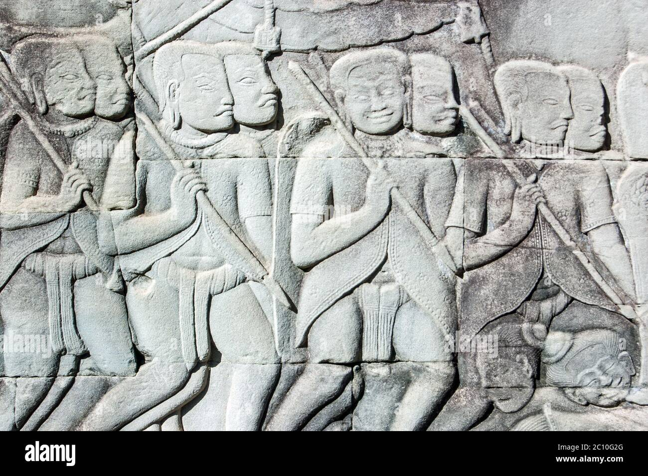 Ancient Khmer bas relief carving showing the Khmer army going into battle. Some of their colleagues are lying drunk on the floor. Outer wall of Bayon Stock Photo