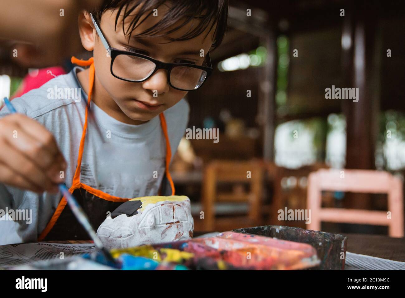 Caucasian boys paint colored crafts in pottery galleries with class friends Stock Photo