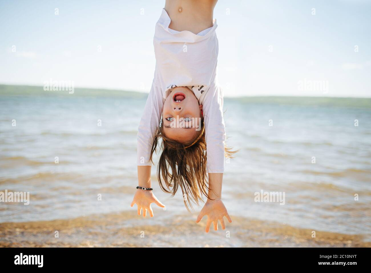 Little hiperemotional school age girl hanging upside down. On a lake shoreside. Stock Photo