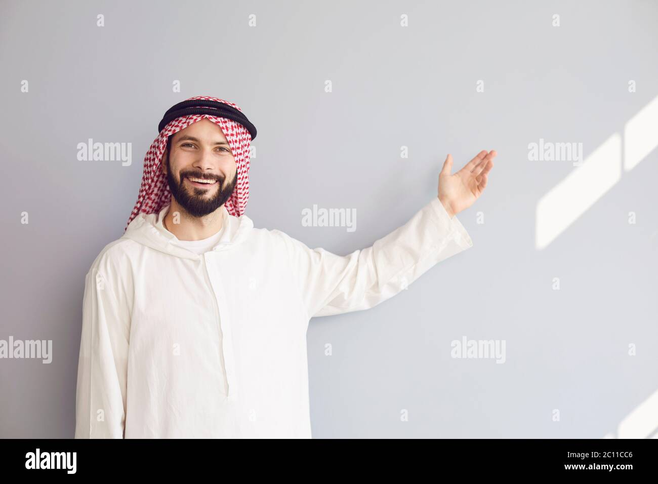 Attractive smiling arab man points his hand to a gray background for text. Stock Photo