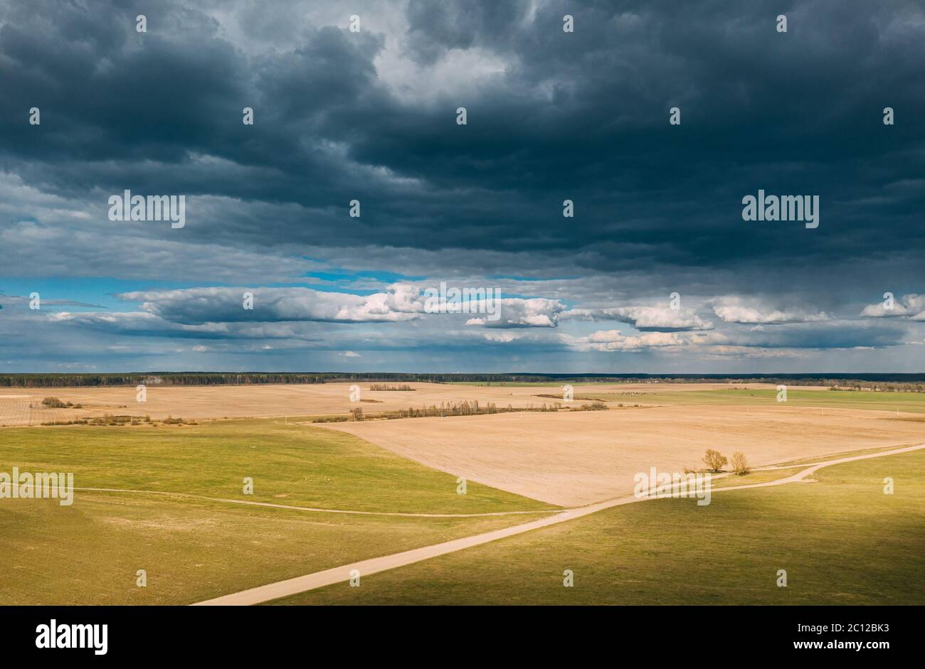 Aerial View. Amazing Natural Dramatic Sky With Rain Clouds Above Countryside Rural Field Landscape In Spring Day. Scenic Sky With Fluffy Clouds On Stock Photo