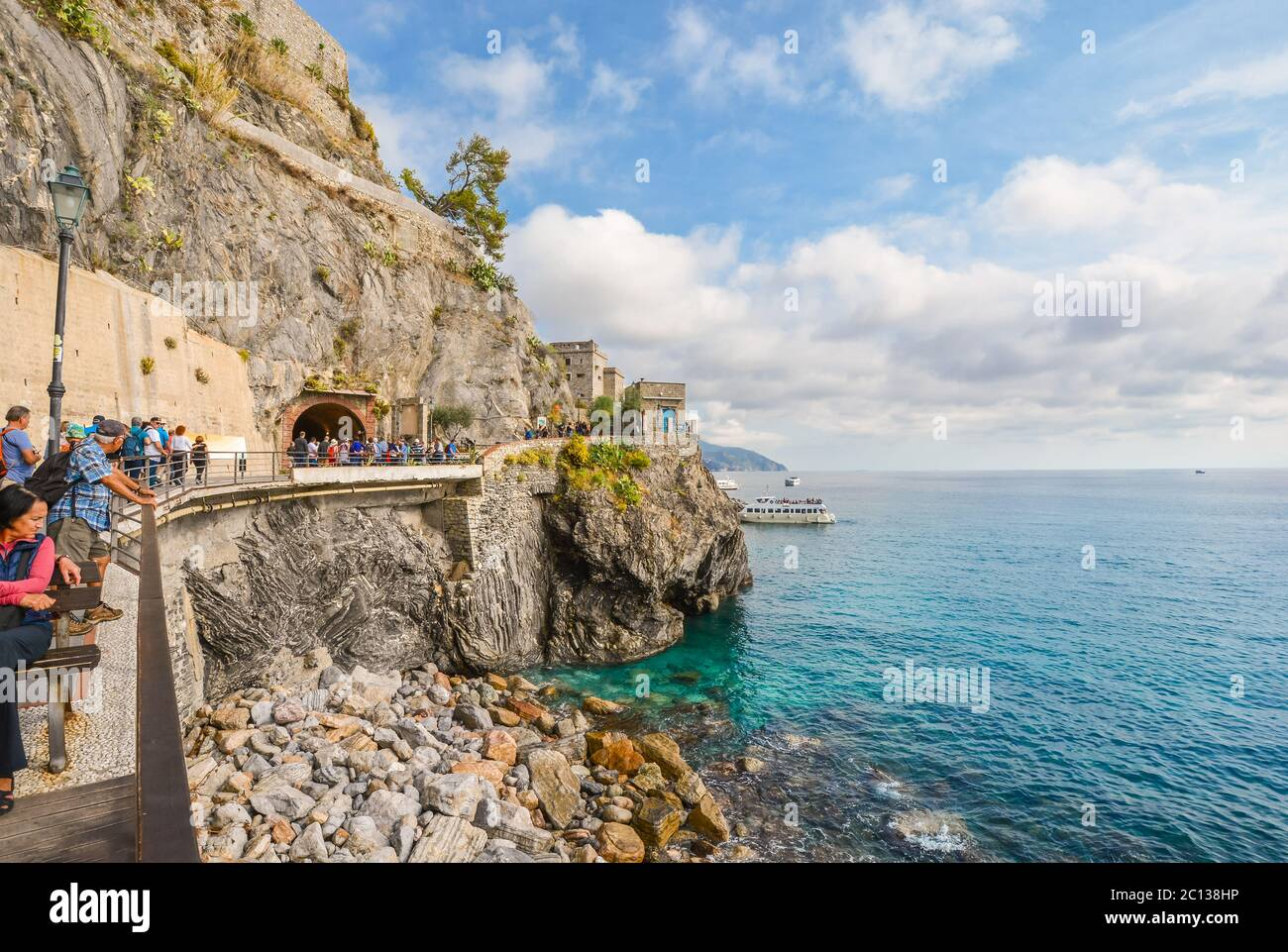 Tourists walk the path and enter the tunnel on the coast of Monterosso al Mare, Cinque Terre Italy, with the Monterosso castle in view over the sea Stock Photo