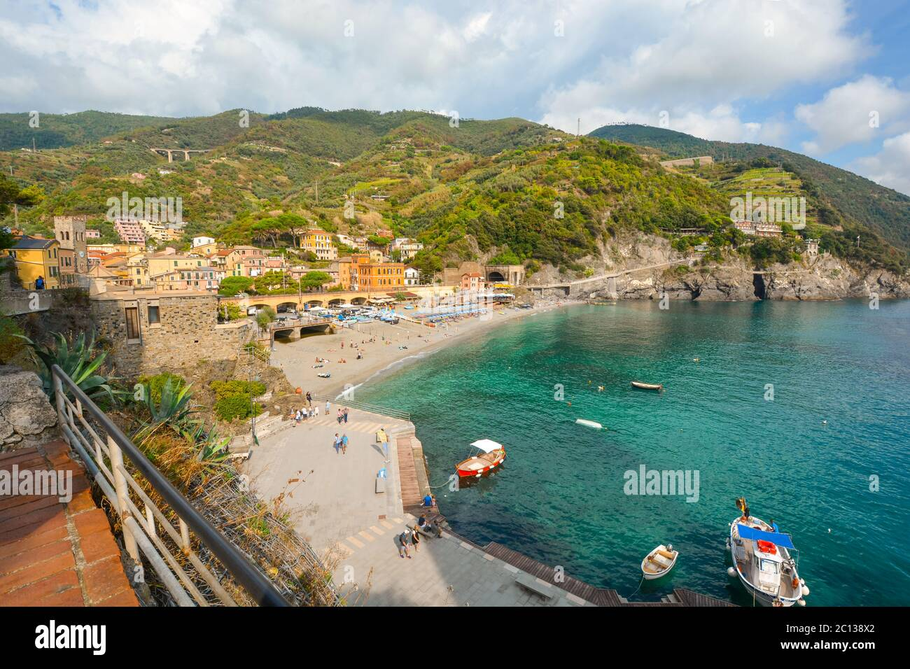 The sandy beach Spiaggia di Fegina at the old side of the Cinque Terre Italy resort village of Monterosso al Mare with tourists and boats in the sea Stock Photo