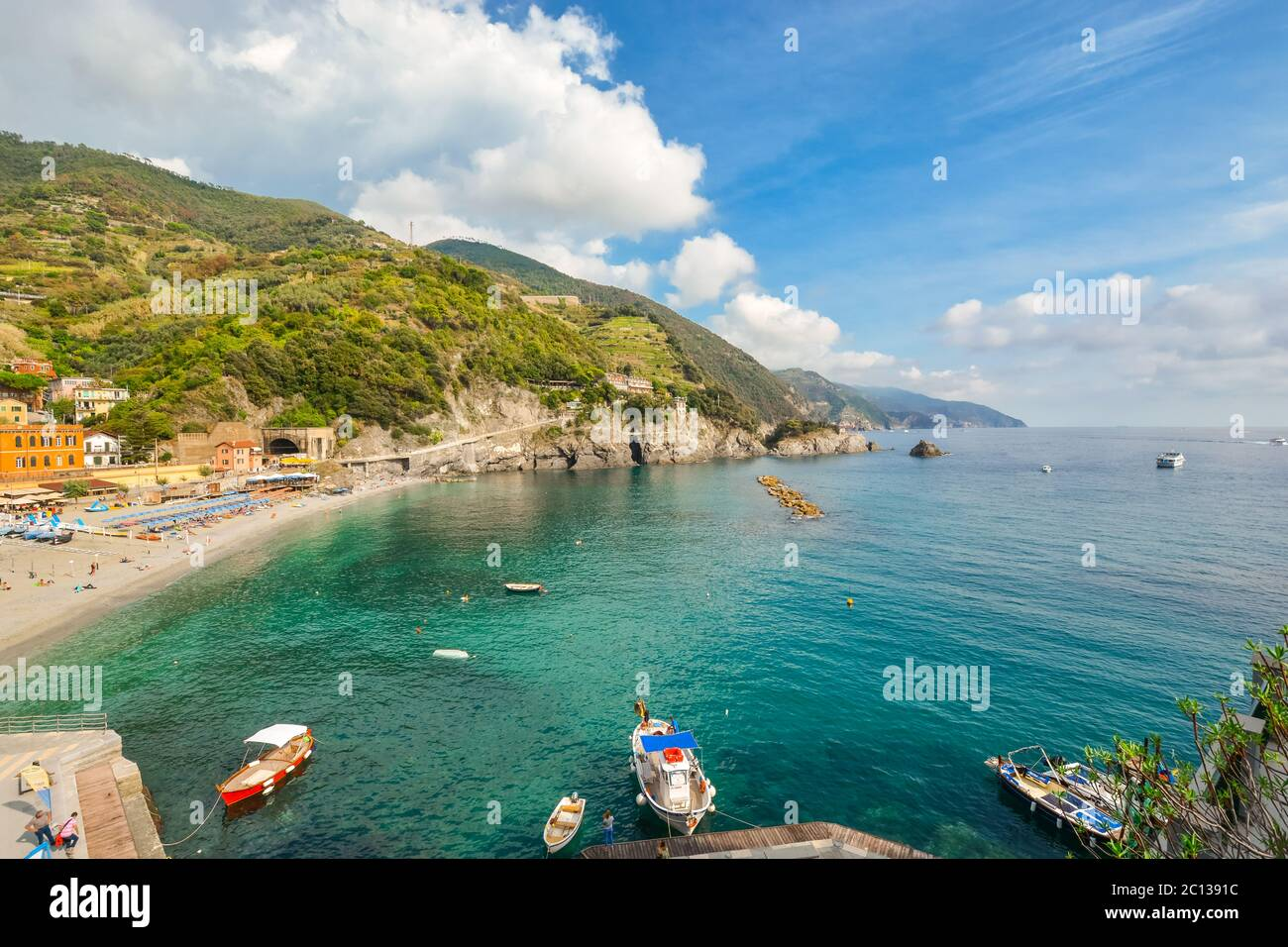 The sandy beach at Monterosso al Mare, Cinque Terre Italy with boats in the sea and the coastline stretching behind Stock Photo