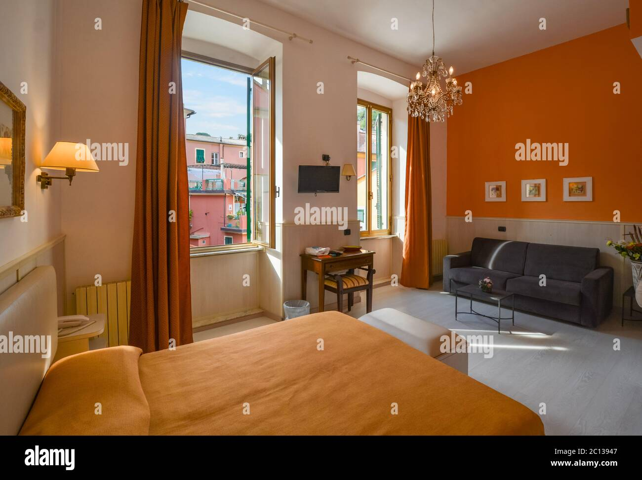 A bright room with large windows and a high ceiling overlooking a colorful Italian village. Stock Photo
