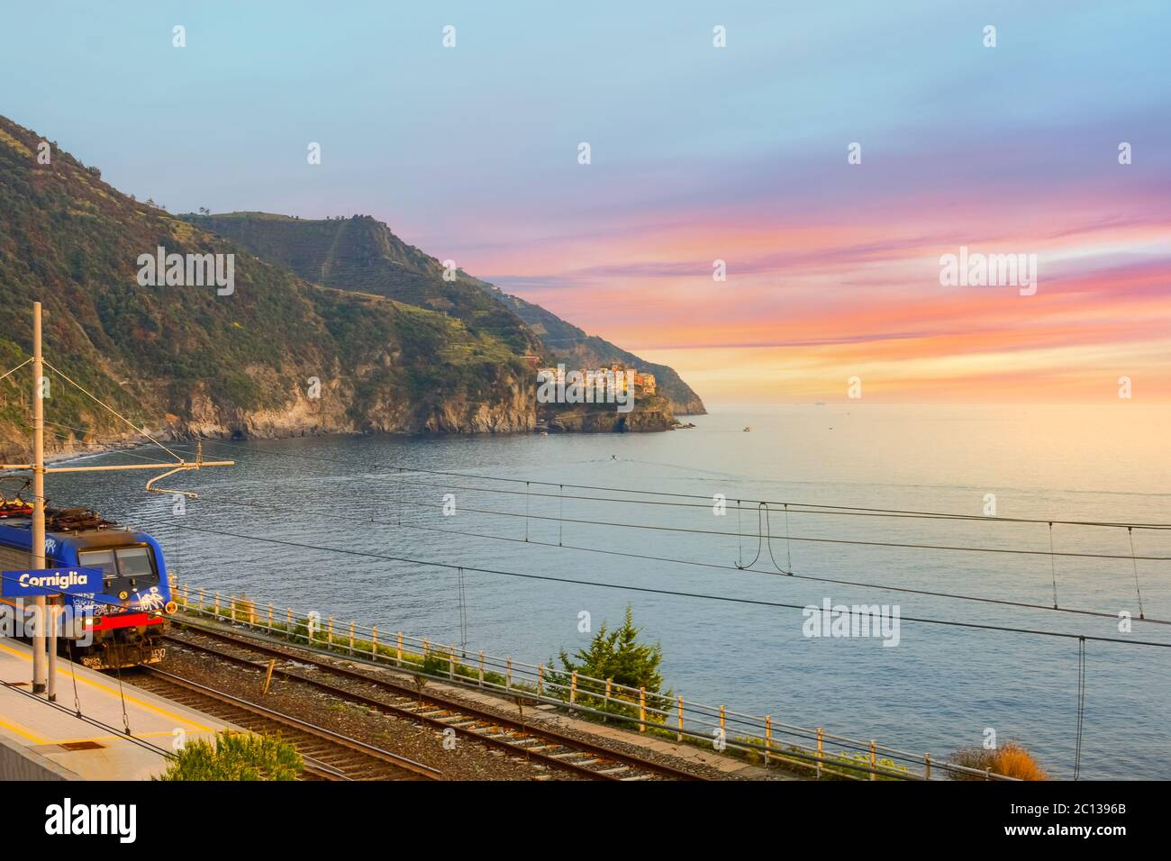 Sunset on the Cinque Terre as the train heads into the Corniglia railway station on the coast of Italy Stock Photo