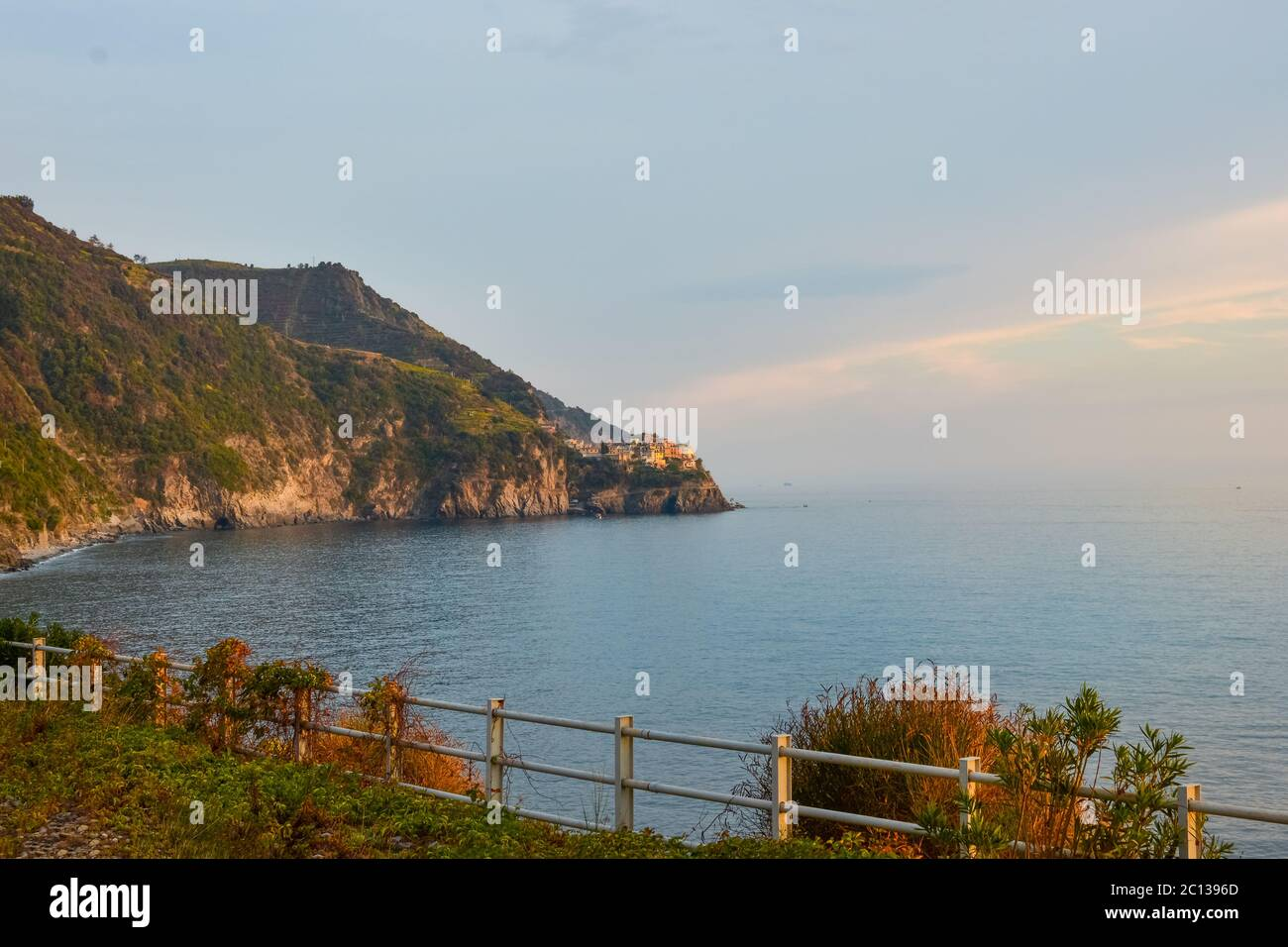 The coastline of Cinque Terre Italy and the Ligurian Sea, with the village of Corniglia in the distance as the sun sets in early Autumn Stock Photo