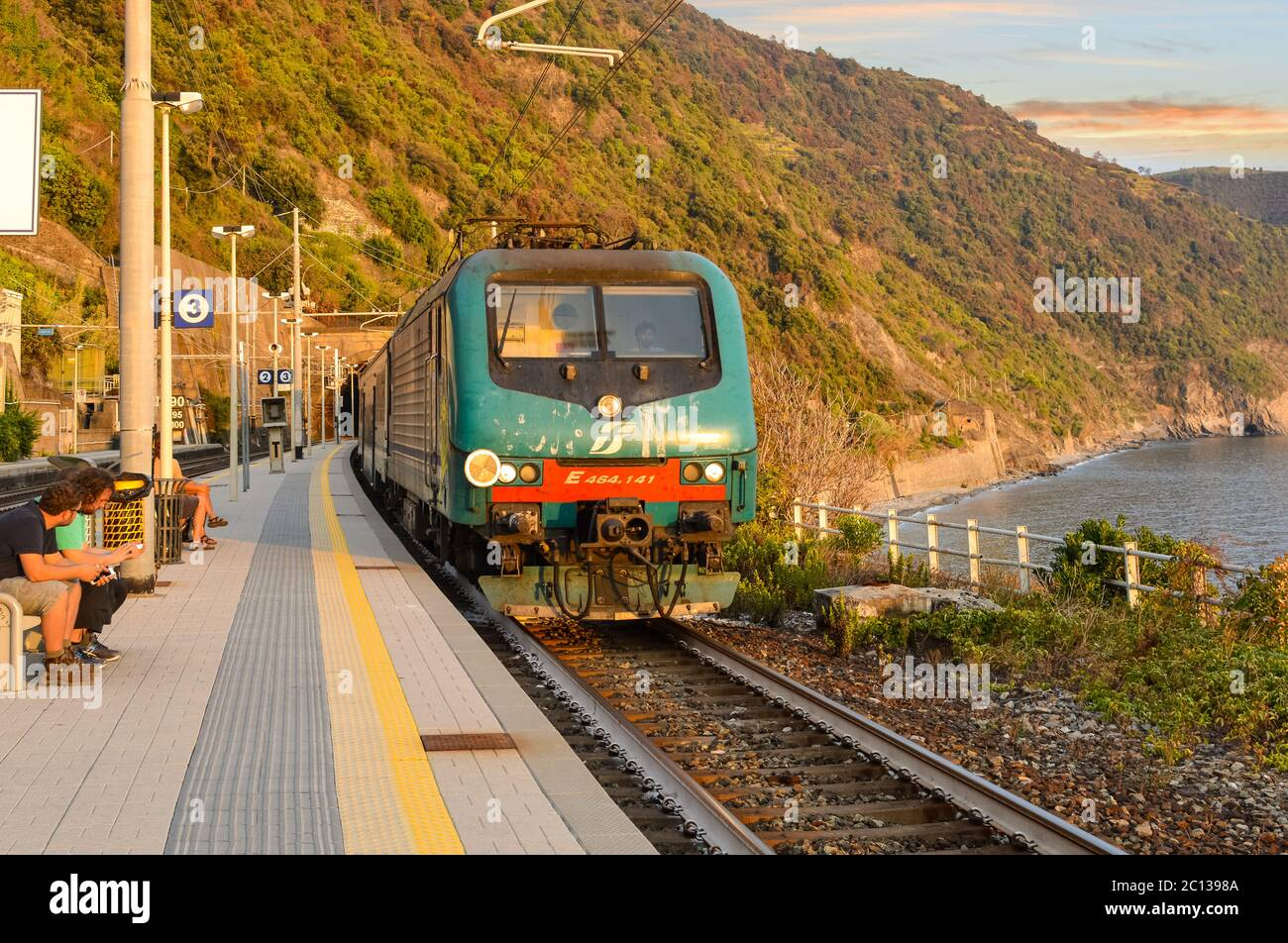 A train travels into the Monterosso al Mare train station on the Cinque Terre coast of Italy as travelers sit and enjoy a warm day in early autumn Stock Photo