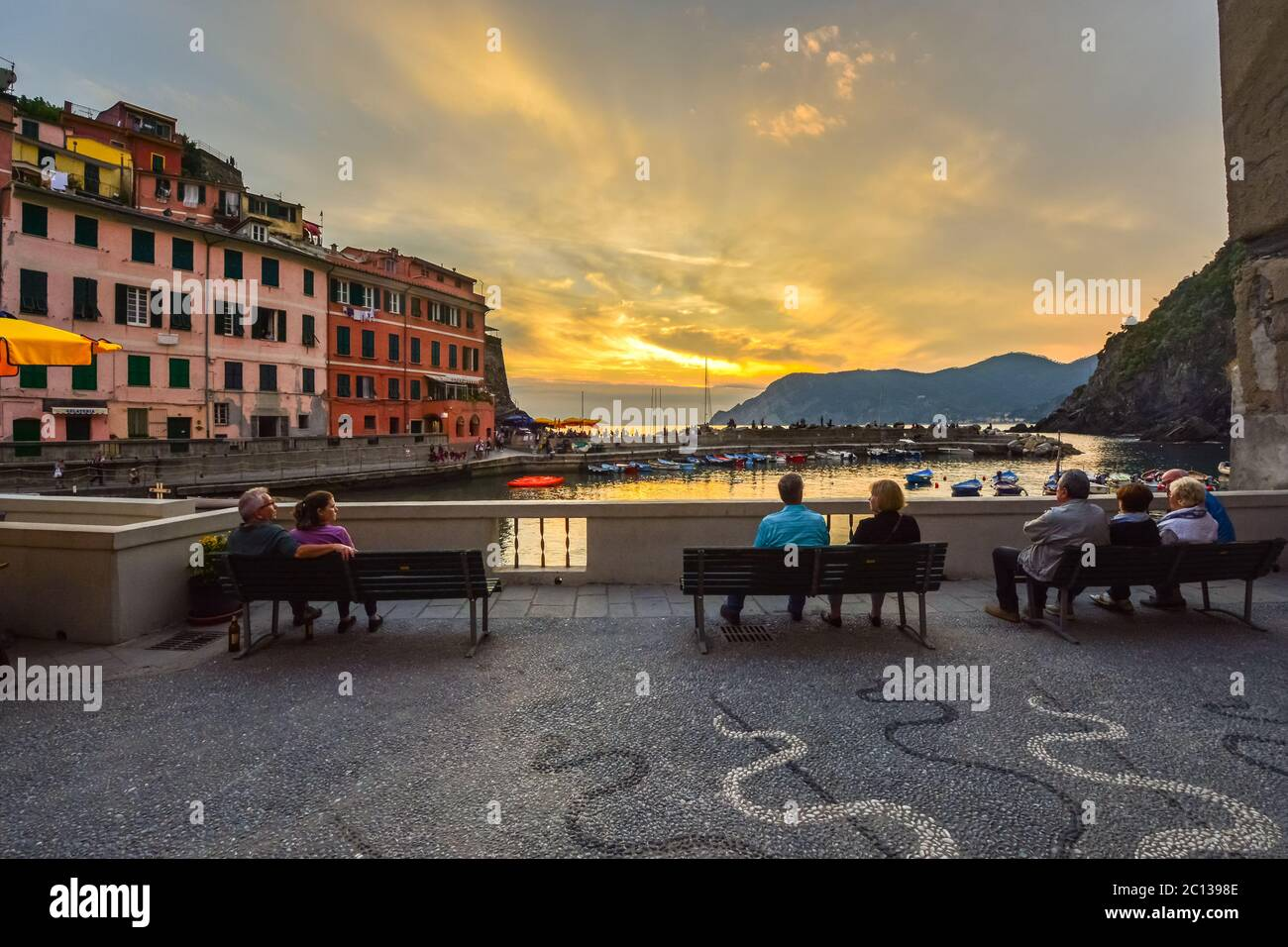 Tourists enjoy a colorful sunset over the Ligurian sea as they sit on a terrace near the small harbor in the Cinque Terre village of Vernazza, Italy Stock Photo