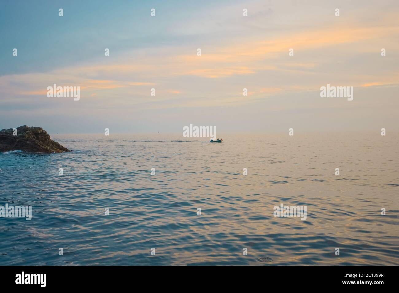 View from the Vernazza Harbor in Cinque Terre, Italy, as a small boat heads out towards the sunset on the Ligurian coast. Stock Photo