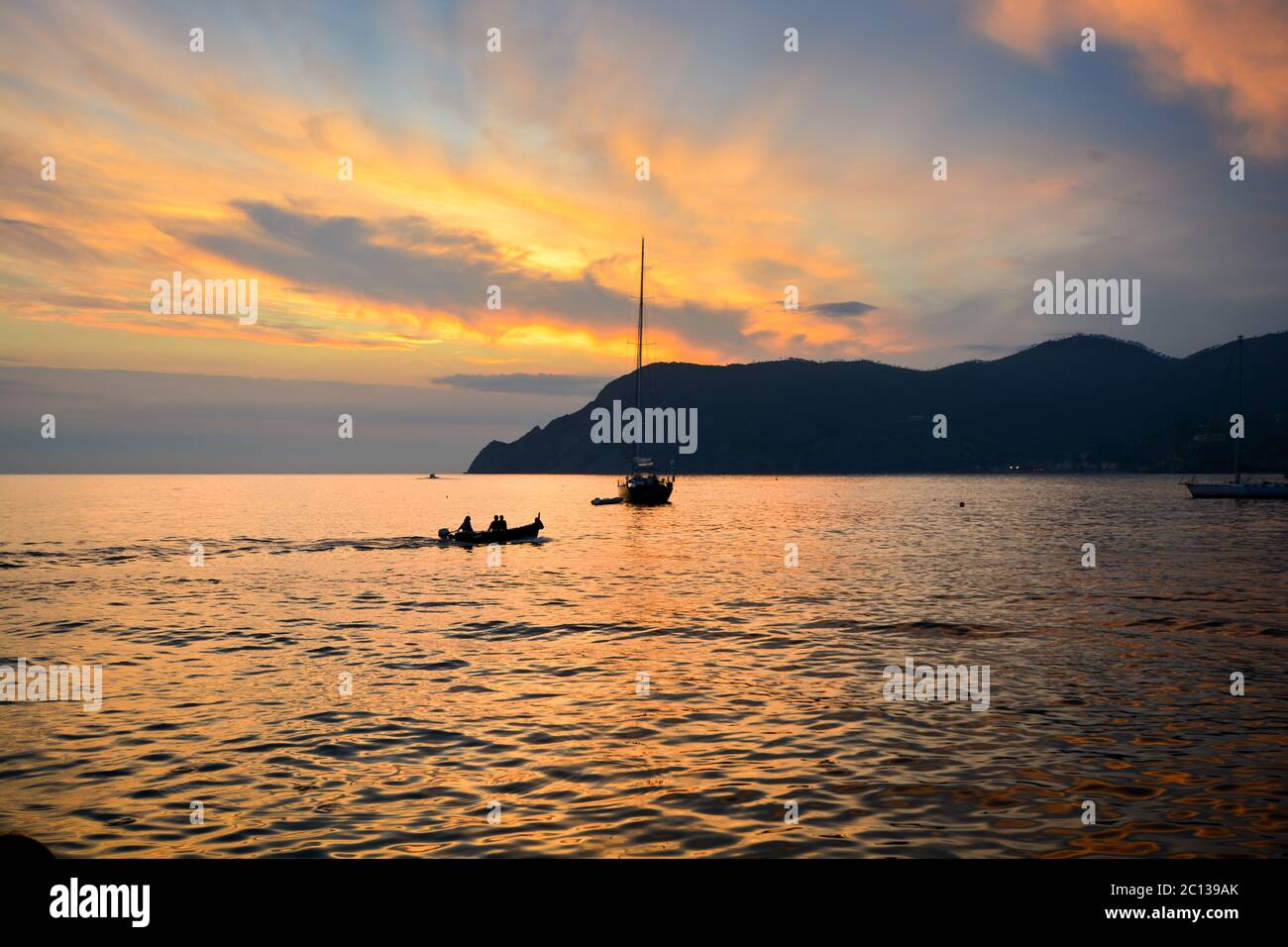 Two boats along the Ligurian coast of Vernazza harbor at sunset along the Cinque Terre, Italy Stock Photo