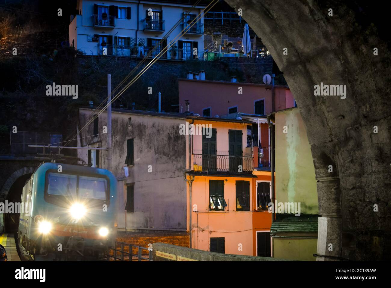 A night train's headlights shine as it enters a tunnel in the evening at Vernazza Italy, on the Cinque Terre coast with the hillside town behind Stock Photo