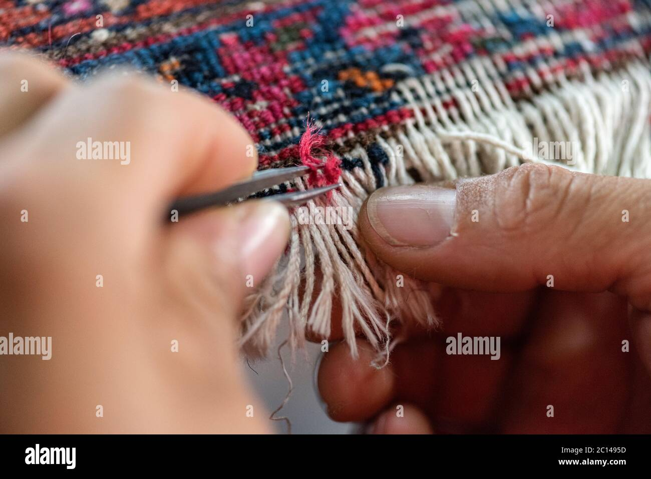 traditional hand sewing fixing old vintage antique persian carpet up close Stock Photo