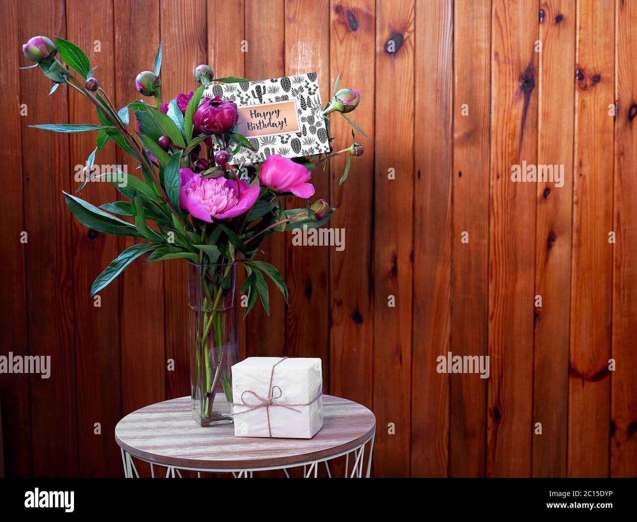Pink flowers peonies in a vase on a wooden background with a small white gift and a happy birthday card. The photo was taken with natural daylight. Stock Photo