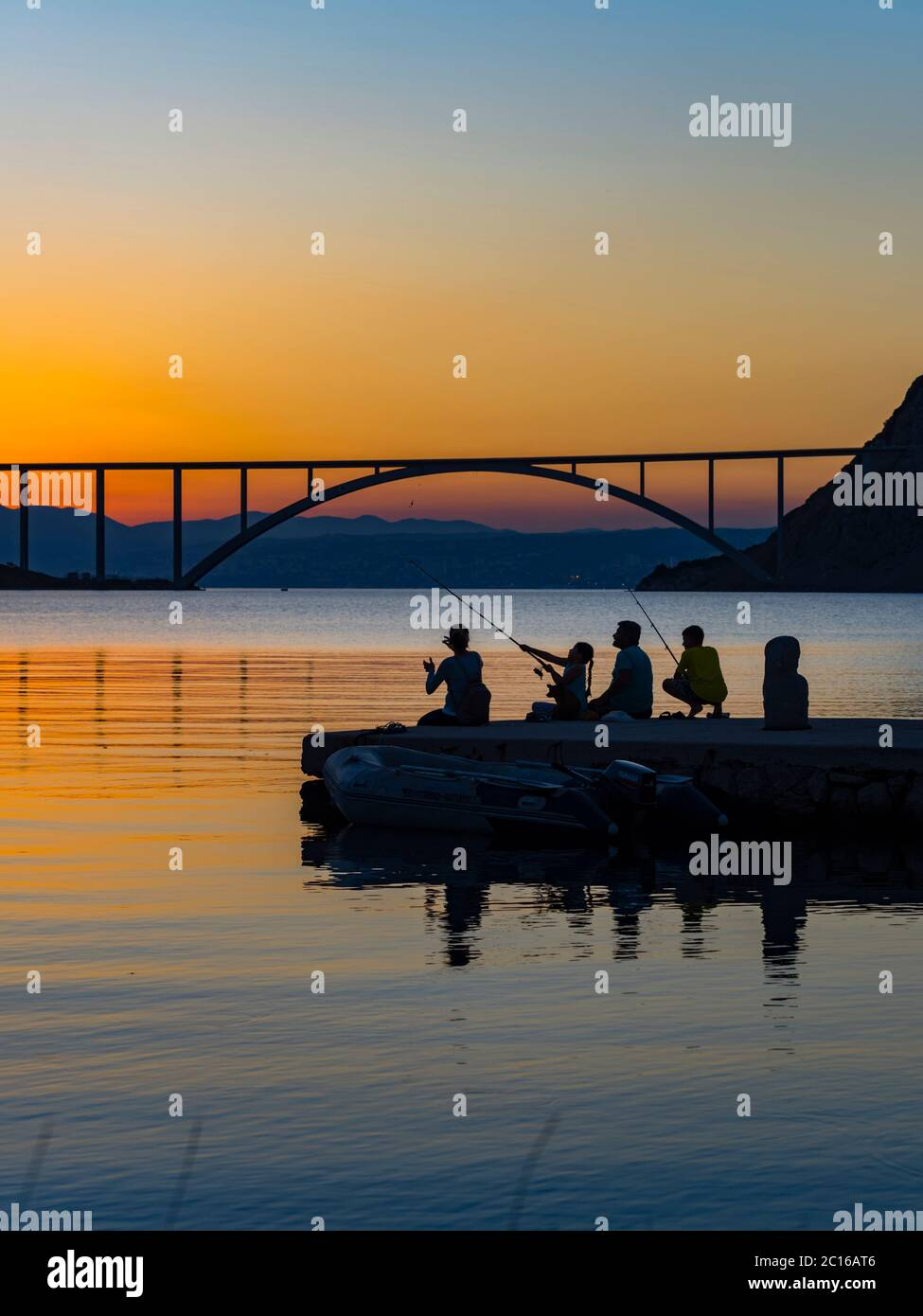 Family together dusk evening free time fishing bridge mainland to island Krk in background silhouettes silhouetting silhouette pretty picturesque Stock Photo