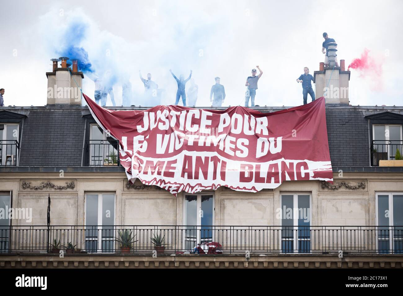 Paris, France. 13th June, 2020. Members of a right wing group that hung a banner in support of victims of anti-white racism cheer and light flares on top of a building at Place de la Republique during a Black Lives Matter protest in paris, France, on June 13th, 2020. (Photo by Daniel Brown/Sipa USA) Credit: Sipa USA/Alamy Live News Stock Photo