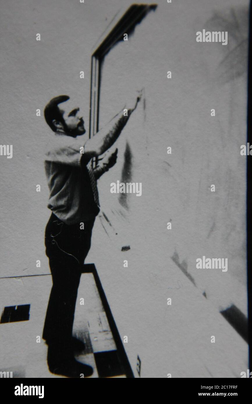 Fine 70s vintage black and white extreme photography of a teacher standing at the chalkboard and writing on it. Stock Photo