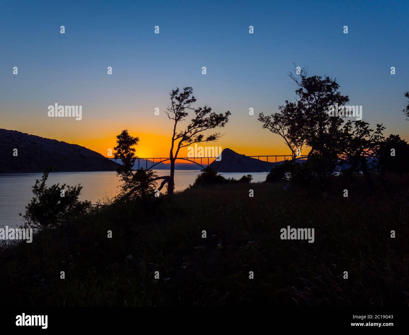 Sunset landscape silhouette silhouetting trees bridge mainland to island Krk Croatia Stock Photo