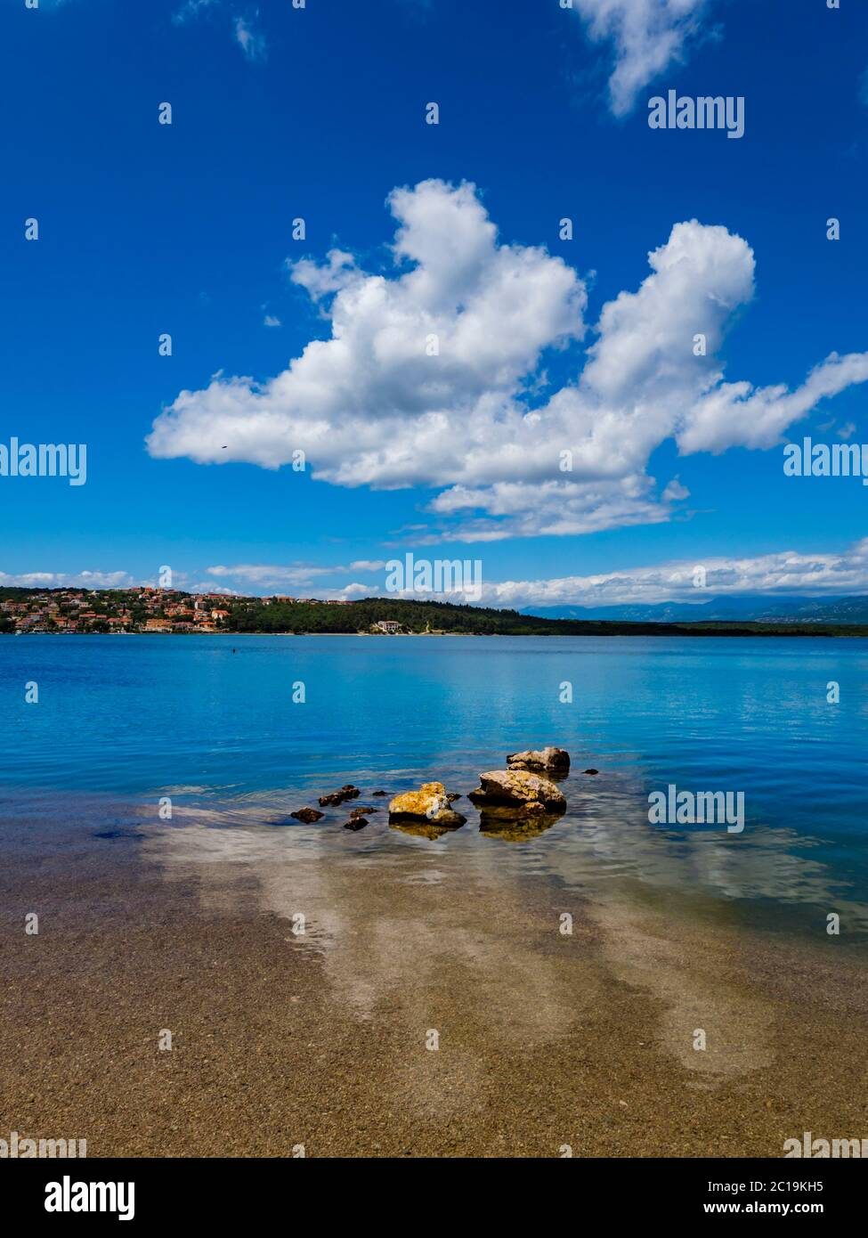 Pretty beach scenery in Soline on island Krk Croatia bunch of rocks protruding from sea surface immersed Summer clouds reflected in water Stock Photo