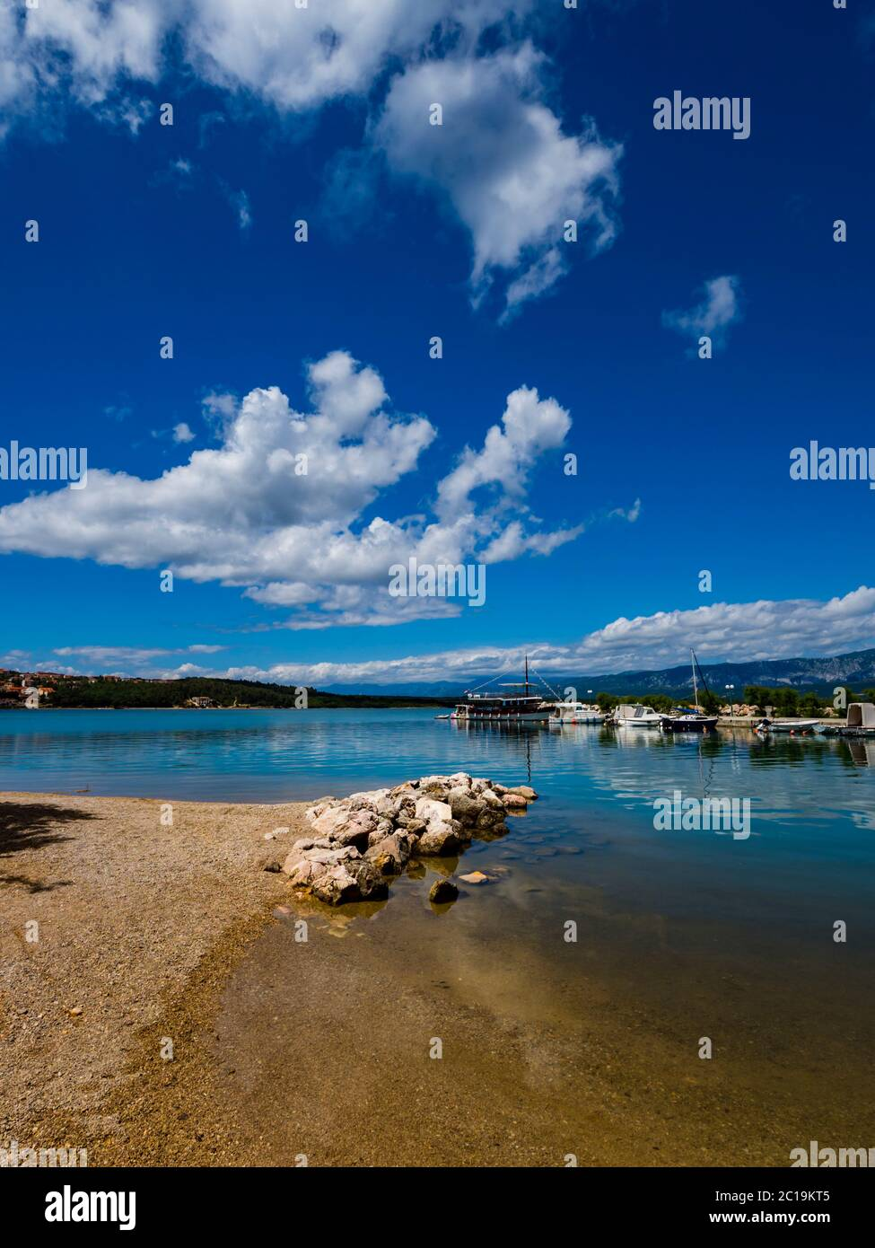 Pretty sand beach scenery in Soline on island Krk Croatia bunch of rocks protruding from sea surface immersed Summer clouds reflected in water Stock Photo