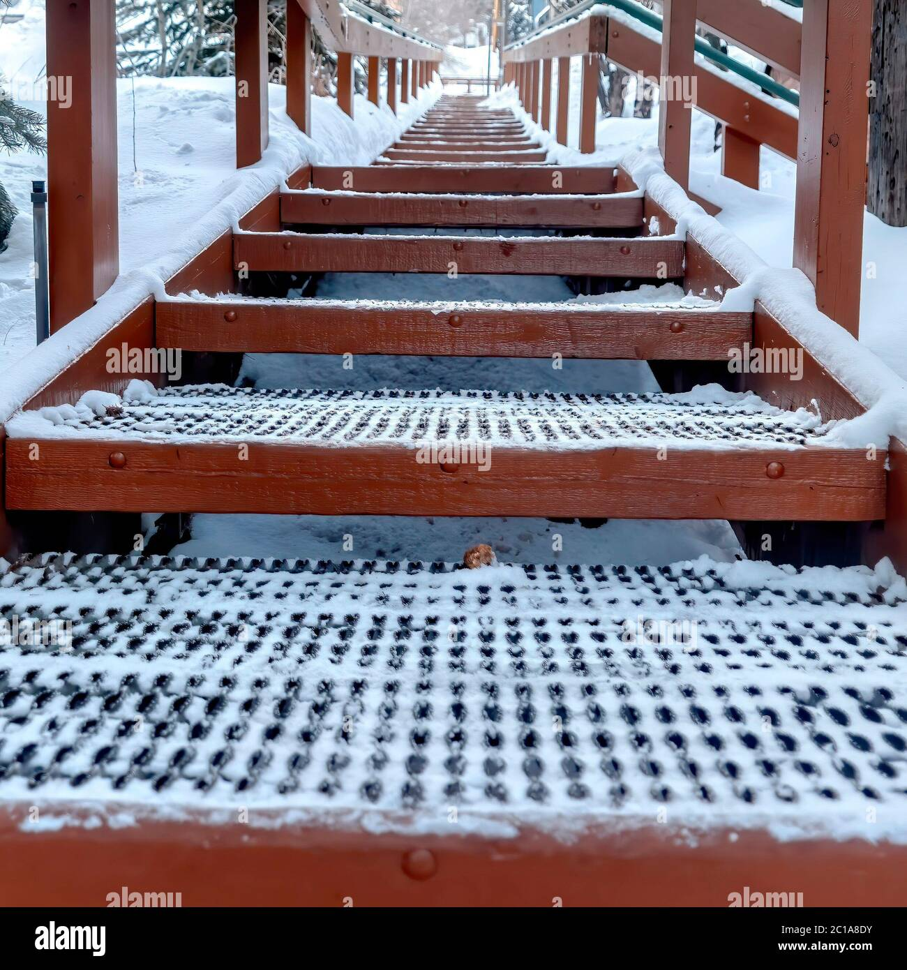 Square Focus on grate metal treads of outdoor stairs against snowy hill in winter Stock Photo